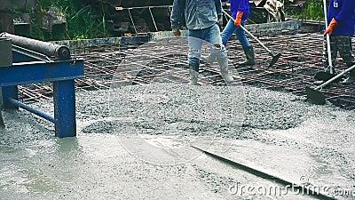 Trabalhador do homem que usa uma cesta de aço concreta para o cimento após ter derramado concreto pronto-misturado filme