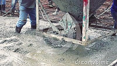 Trabalhador do homem que usa uma cesta de aço concreta para o cimento após ter derramado concreto pronto-misturado vídeos de arquivo