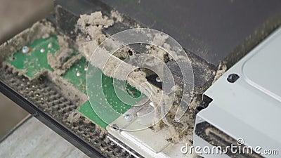 Trabalhador repara um console de jogo no qual muito pó Trabalhador repara um console de jogo no qual muita poeira video estoque