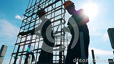 Trabalhadores da construção estão fazendo uma carcaça de metal ao ar livre filme
