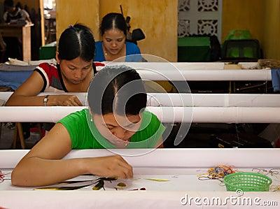 Trabalhadores de matéria têxtil em uma fábrica pequena Foto Editorial
