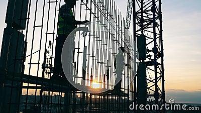 Trabalhadores masculinos estão caminhando ao longo da carcaça do prédio em andamento filme