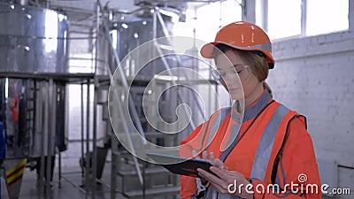 Trabalho fêmea pesado, retrato da menina do coordenador no capacete e combinações com o portátil da tabuleta que faz decisões cal filme