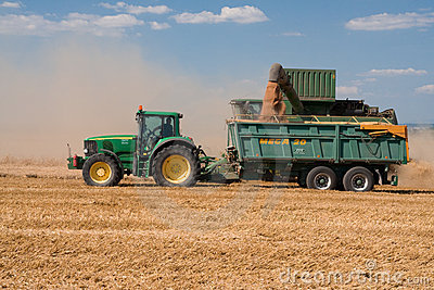Tractor and combine John Deere on harvested field Editorial Image