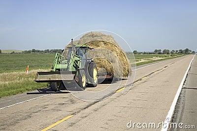 Tractor que tira hacia abajo el heno Fotografía editorial