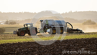Tractor with sprayer at sunrise.