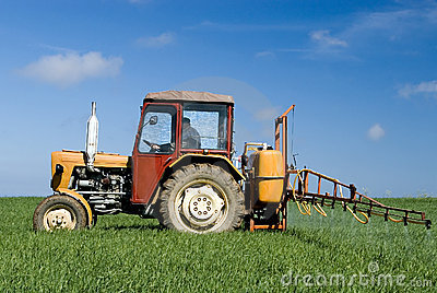 Tractor spraying green field