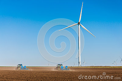 Tractors working on crop field near wind turbines