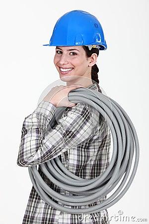Tradeswoman carrying corrugated tubing