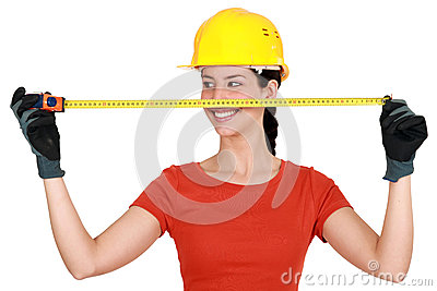 Tradeswoman using a measuring tape