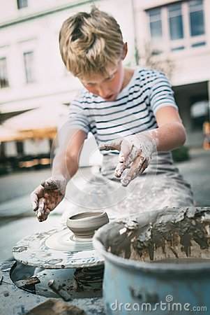 Traditional craft lesson: boy try to make a pottery bowl Stock Photo