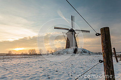 Traditional Dutch windmill in winter during sunset
