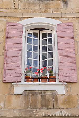 Traditional French window with pink shutters