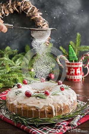 Traditional homemade Christmas cake with garnish cranberry and rosemary on decorative plate. Powdering with icing sugar. Stock Photo