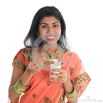 Traditional Indian woman eating yogurt