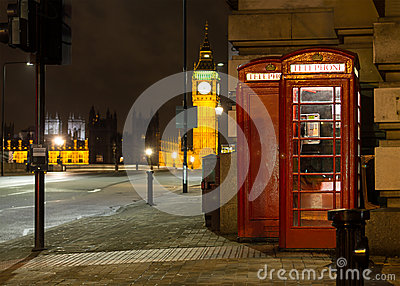 Traditional red phone booth in London with the Big Ben in the ba