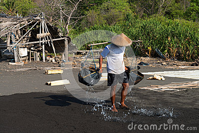 Traditional sea salt production on on the volcanic black sand, B