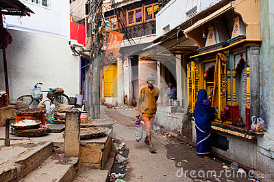 Traditional street life with a sellers, a praying woman and passers-by people Editorial Stock Photo