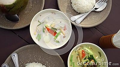 Traditionell asiatisk kokkonst på tabellen Bästa sikt av autentisk thai disk curry, tom khasoppa och ris lager videofilmer