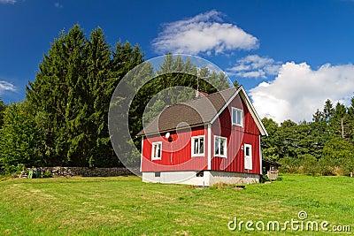Traditionellt rött svenskt hus på skogen