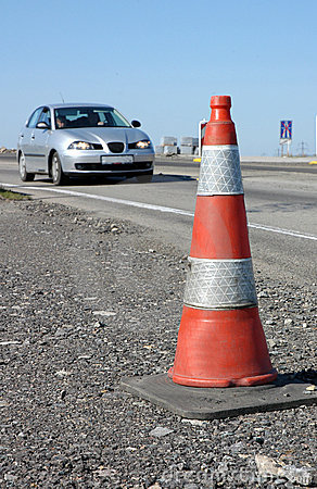 Traffic cone on road with car