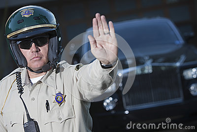 Traffic Cop Signaling Stop Gesture With Car In Background