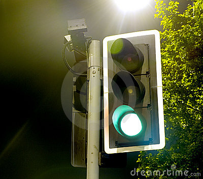 Traffic Lights near a Bright Lamp at Night