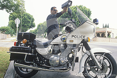 Traffic motorcycle cop pointing radar gun, Editorial Stock Photo