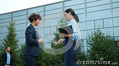 Trage beweging van vrolijke zakenvrouwen die buiten de straat over werk discussiëren stock video