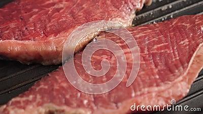 Trage bewegingsopname van Cooking Chief flip rib eye steak met kruiden op grillpan stock videobeelden