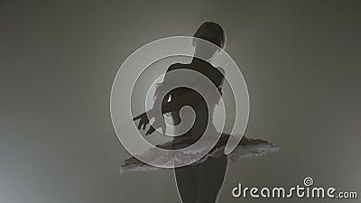 Tragende weiße Ausstattung der würdevollen sinnlichen Ballerina, die elegant in einen dunklen Hintergrund mit Scheinwerfer tanzt  stock footage