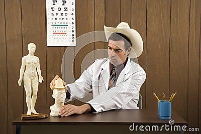Tragender Cowboyhut des männlichen Doktors, der mit Figürchen spielt.
