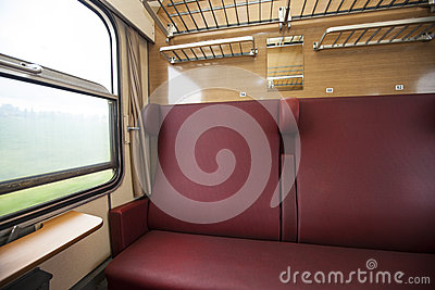 Train compartment with red seats with the view
