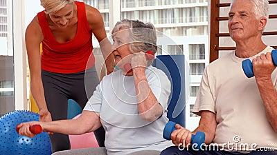 Trainer die bejaarden helpen uitwerken stock video