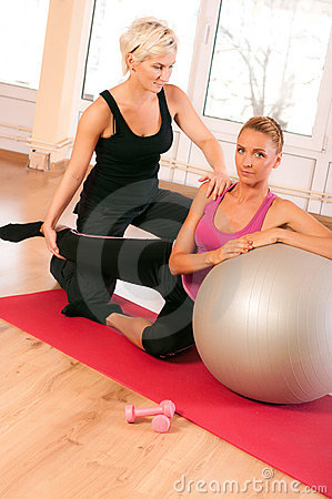 Trainer helping woman in doing exercise on ball
