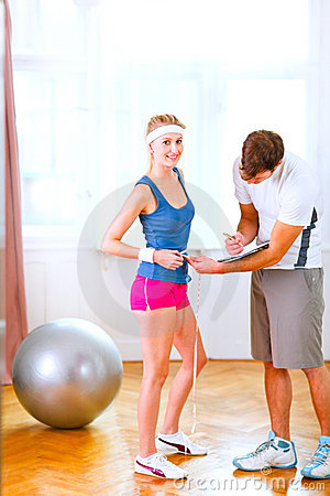 Trainer measuring belly of girl in sportswear