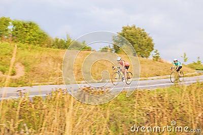 Training process of two female caucasian sportswomen riding bike