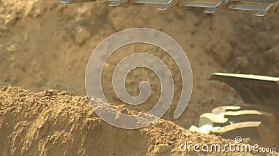 Traktorladdare som hämtar upp jord i en stor hink under bygget av väg, bakgrund, industri, 4 K stock video