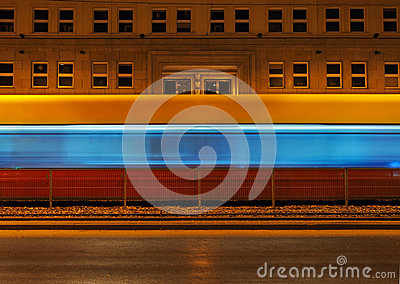 Tram passing the background night scenery building