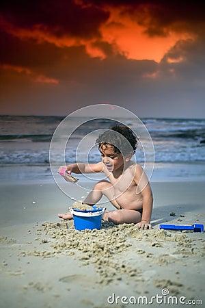 Tramonto della spiaggia del gioco del ragazzo
