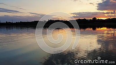 Tramonto meraviglioso sopra l'orizzonte della città con la riflessione sull'acqua calma del lago in una sera silenziosa di estate archivi video