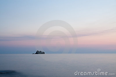 Tranquil view with rock at sunset