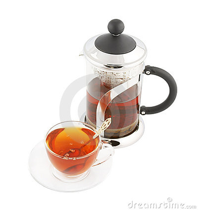 Transparent cup of tea with spoon and teapot