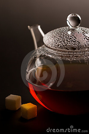 Transparent teapot with black tea and sugar