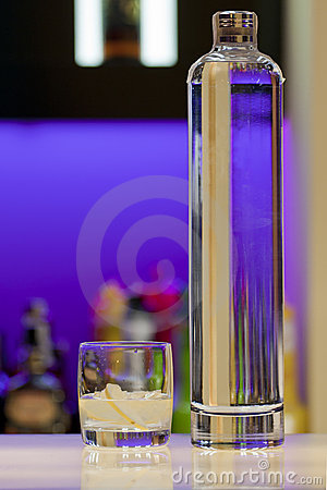 Transparent vodka bottle and glass at the bar