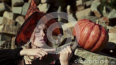 Traum series4 M?dchenspiel mit K?rbisen und Festlichkeit Nette Hexe mit einem Kürbis Überraschte Frau mit Halloween-Kürbis stock video