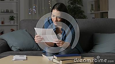 Traurige Frau, die einen Brief in der Nacht lesend sich beschwert
