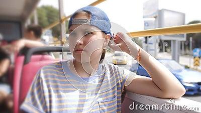 Traurige Teenagerin in Baseballmütze, die in einem Bus ohne Fenster fährt stock video