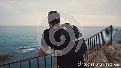 Trauriger erwachsener Mann passt allein auf Meerblick auf, wenn er Zeit vom Felsen glättet stock video footage