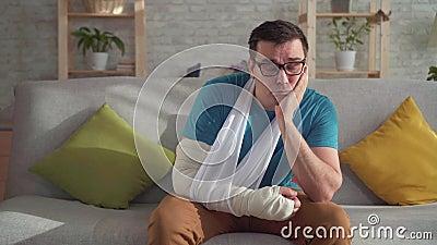 Trauriger junger Mann in den Gläsern mit dem gebrochenen Arm stock video